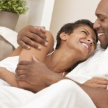A happy African American man and woman couple in their thirties sitting at home together cuddling & laughing.