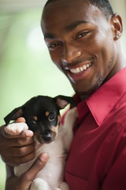 African American man holding puppy