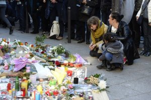 Mourners gather on November 15, 2015 at a memorial site created outside of Le Carillon bar, in the 10th district of Paris, for victims of the November 13 terrorist attacks in Paris. Islamic State jihadists claimed a series of coordinated attacks by gunmen and suicide bombers in Paris that killed at least 128 people in scenes of carnage at a concert hall, restaurants and the national stadium. AFP PHOTO / ALAIN JOCARD (Photo credit should read ALAIN JOCARD/AFP/Getty Images)